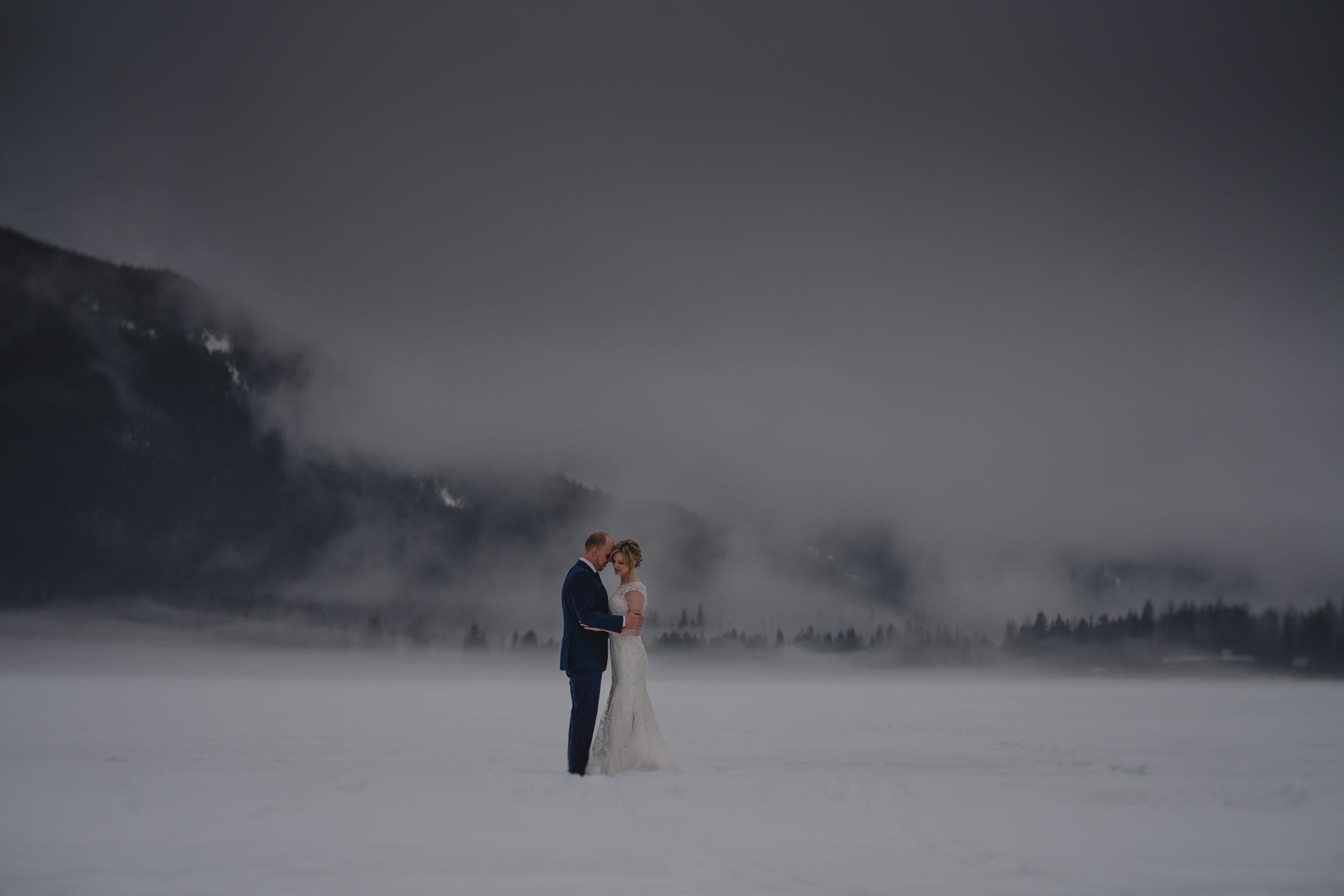 Wedding couple holding on a foggy frozen lake